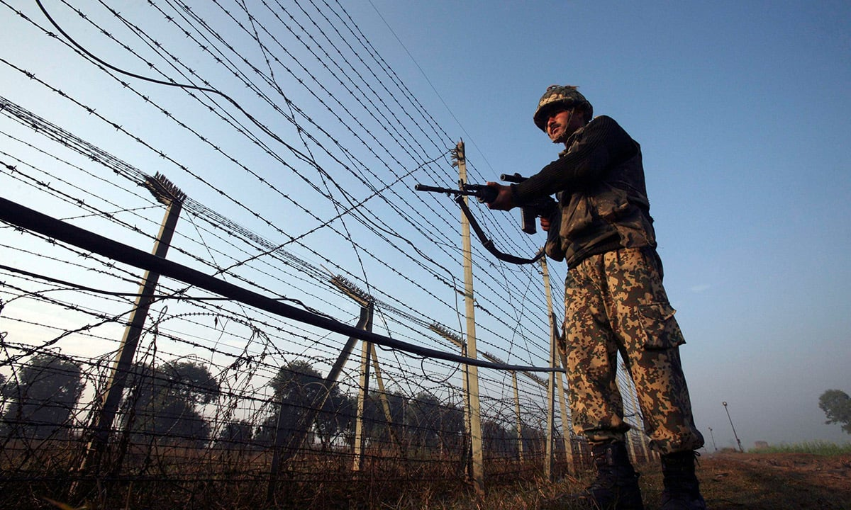 An soldier stands guard at the fenced Pakistan-India border | Reuters