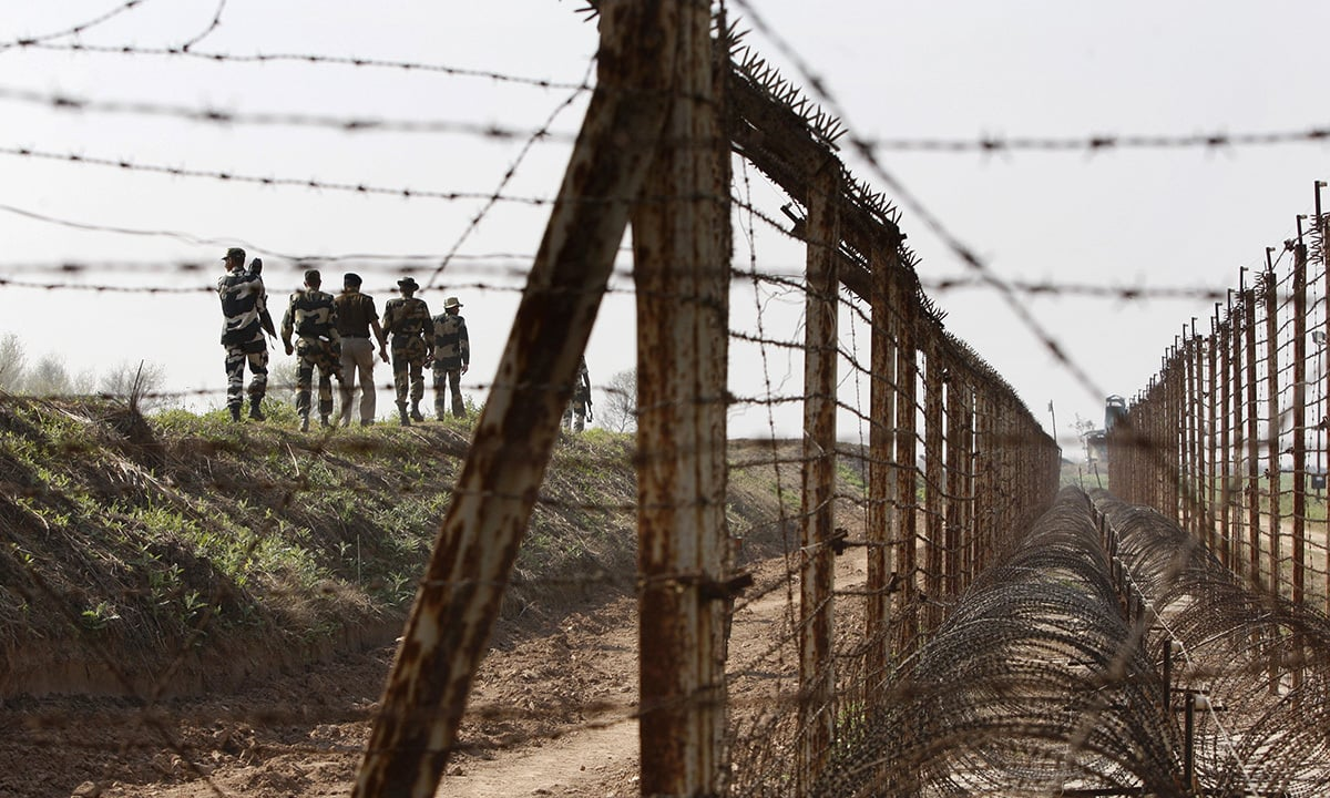 Indian Border Security Force soldiers patrol the fenced border with Pakistan in R.S. Pura sector| AP