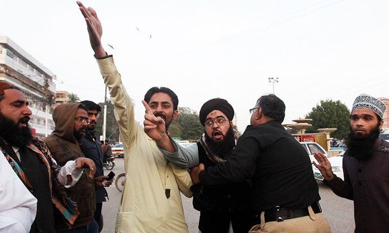 A policeman intervenes as supporters of Tehreek-i-Labaik Ya Rasool Allah group chant slogans during a protest. -Reuters