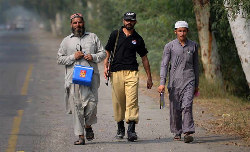A policeman escorts polio vaccination workers in Azakhel, Nowshera. — File photo