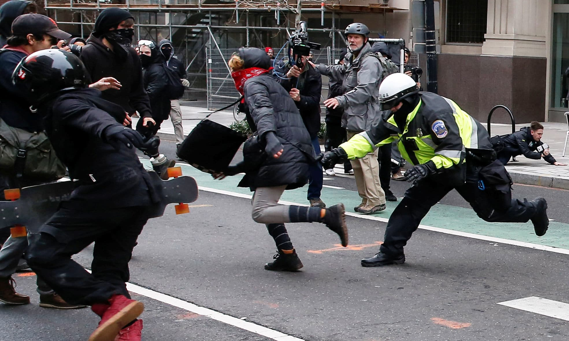 A police officer tries to tackle a protester demonstrating against US President Donald Trump. -Reuters
