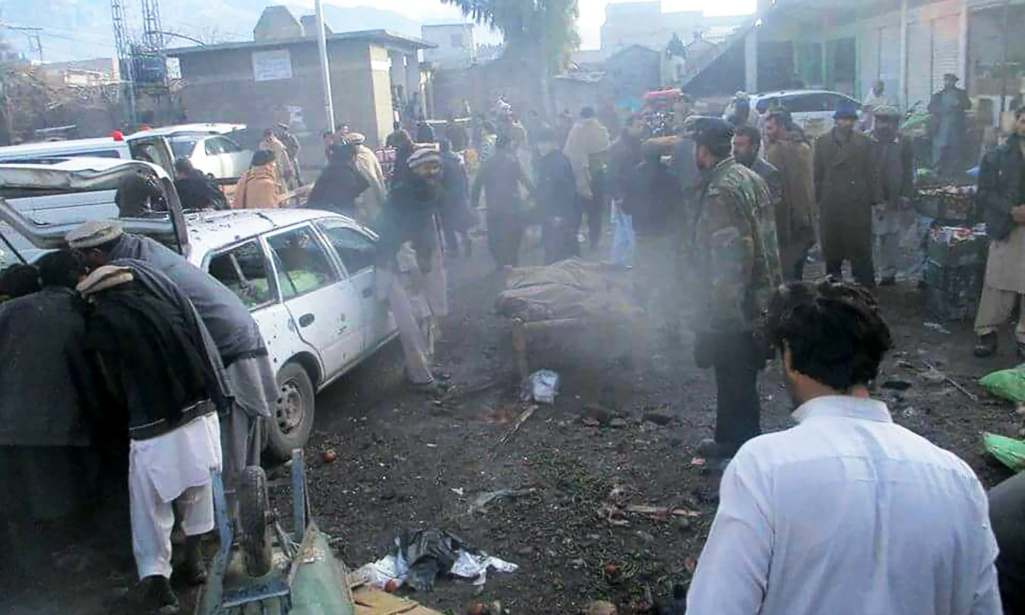 People gather at the site of a bomb explosion at a vegetable market in Parachinar city.—AFP