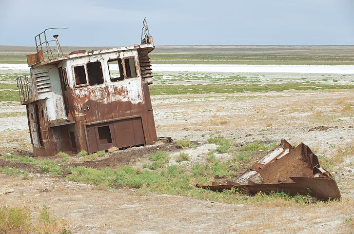 Rusted remains of a fishing boat at the sea bed of the Aral sea, Aralsk, Kazakhstan. Evaporation of one of largest lakes in the world is considered one of the planet's worst environmental disasters