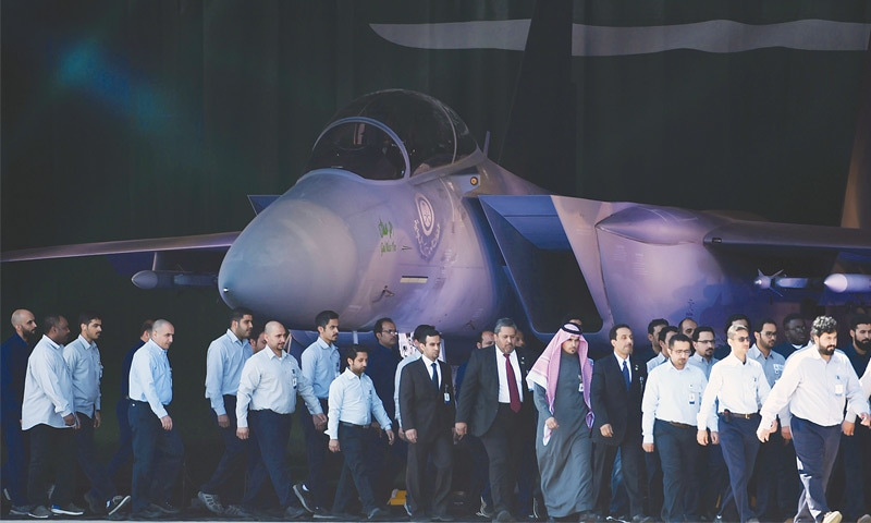 RIYADH: Saudi air force officers and technical staff walk past an advanced F-15SA fighter jet during a ceremony marking the 50th anniversary of the creation of the King Faisal Air Academy on Wednesday.—AFP