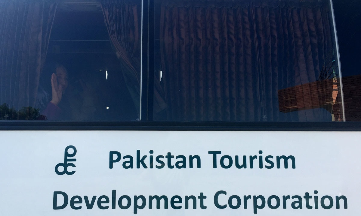 Zaiba waving goodbye while sitting in a PTDC bus in Lahore en route to Delhi
