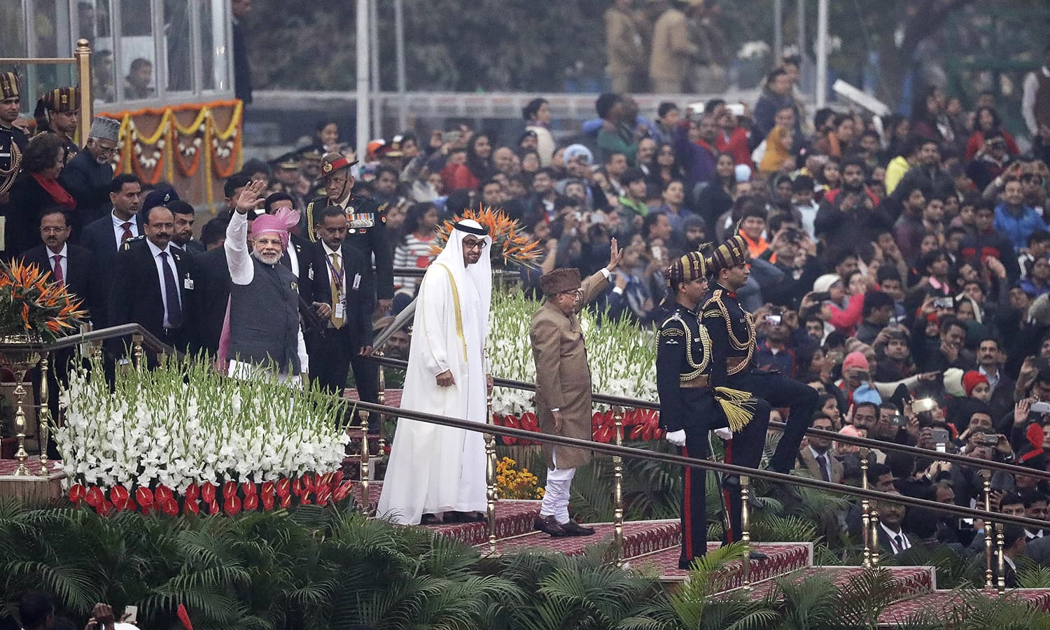 Indian Prime Minister Narendra Modi and Indian President Pranab Mukherjee wave to the crowd as they leave after witnessing the Republic Day parade along with Abu Dhabi's Crown Prince Sheikh Mohammed bin Zayed Al Nahyan, in white robe, in New Delhi.— AP