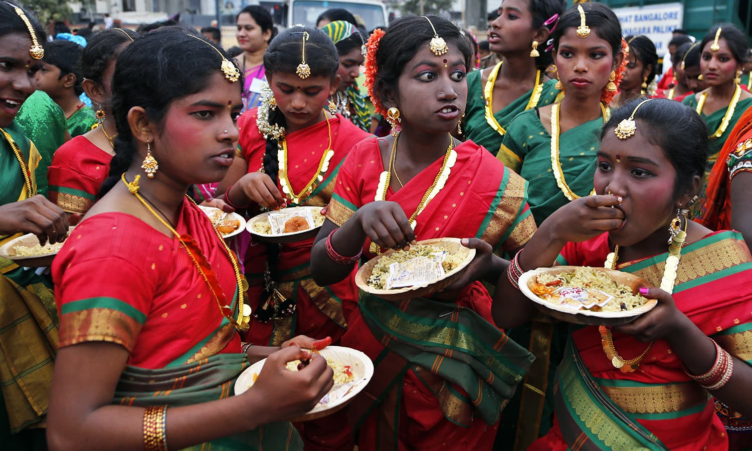 School children dressed in traditional attire eat breakfast before participating in a Republic day parade in Bangalore.— AP
