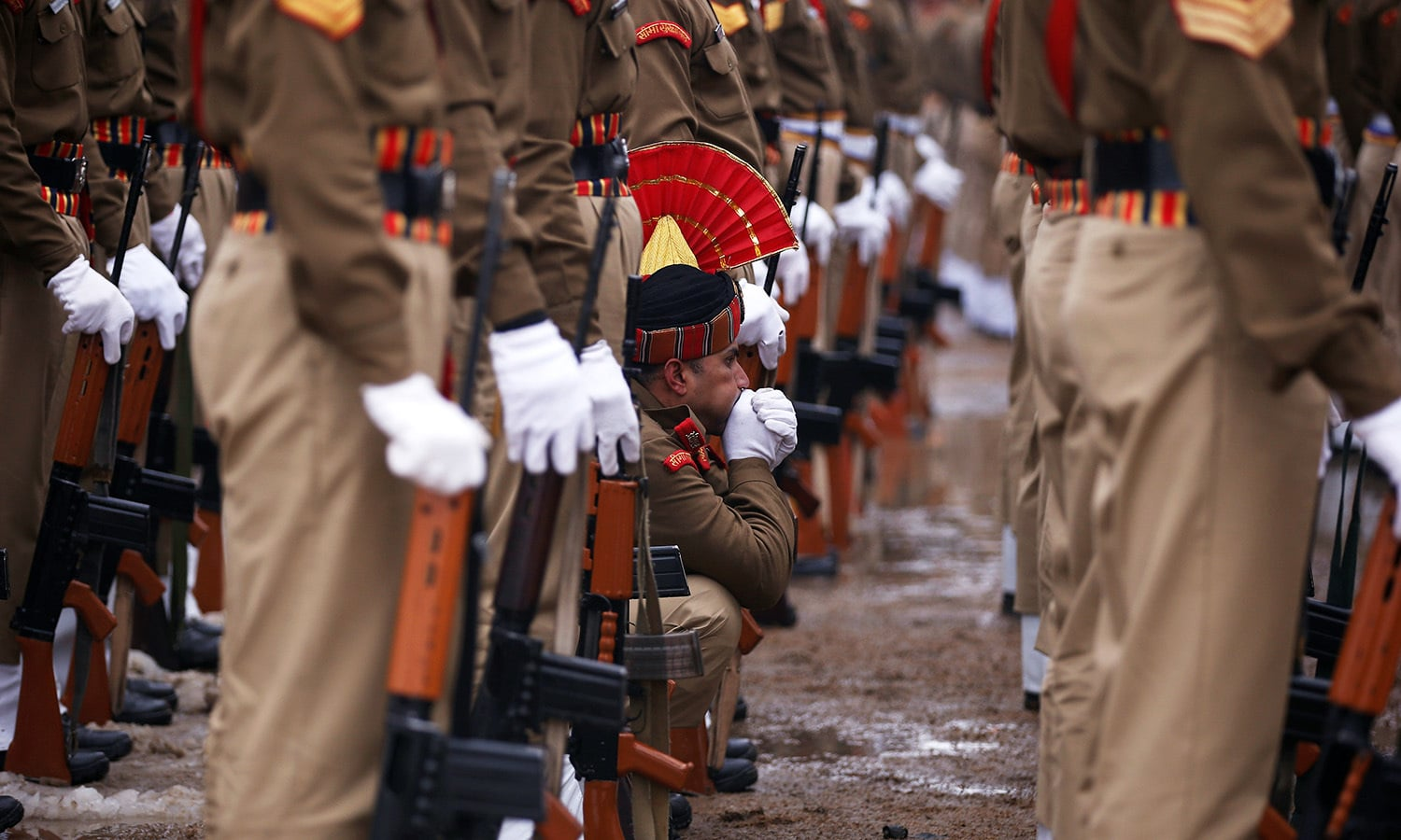 An Indian policeman blows warm air onto his hand as he takes part in a parade to celebrate India's Republic Day on a cold winter day in Srinagar, India-held Kashmir.— Reuters