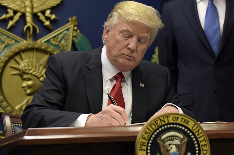 President Donald Trump signs an executive order on extreme vetting during an event at the Pentagon in Washington, Friday, Jan 27.— AP