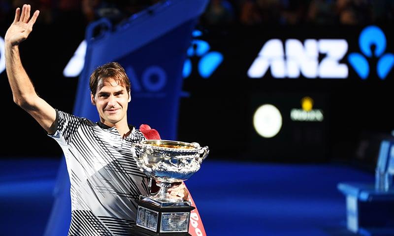 Roger Federer holds the championship trophy after winning the men's singles final match against Spain's Rafael Nadal. -AFP