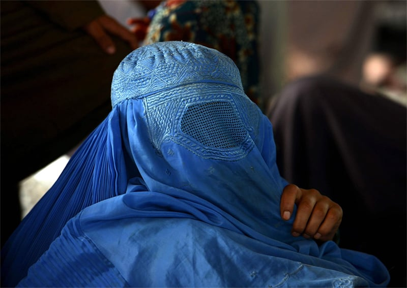 An Afghan refugee woman waits to board a truck at the UNHCR repatriation centre on the outskirts of Peshawar. — AFP