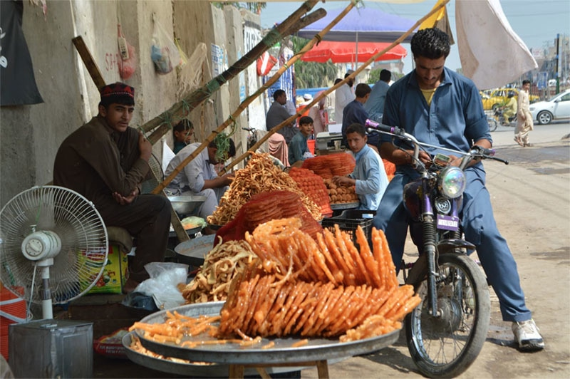 An Afghan vendor selling sweets at a roadside stall in Peshawar. — Malik Achakzai