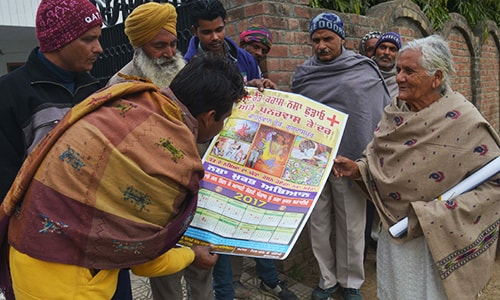 Indian activist Asha Rani, 76, carries posters during a campaign against drug addiction in a village near the town of Gurdaspur. — AFP