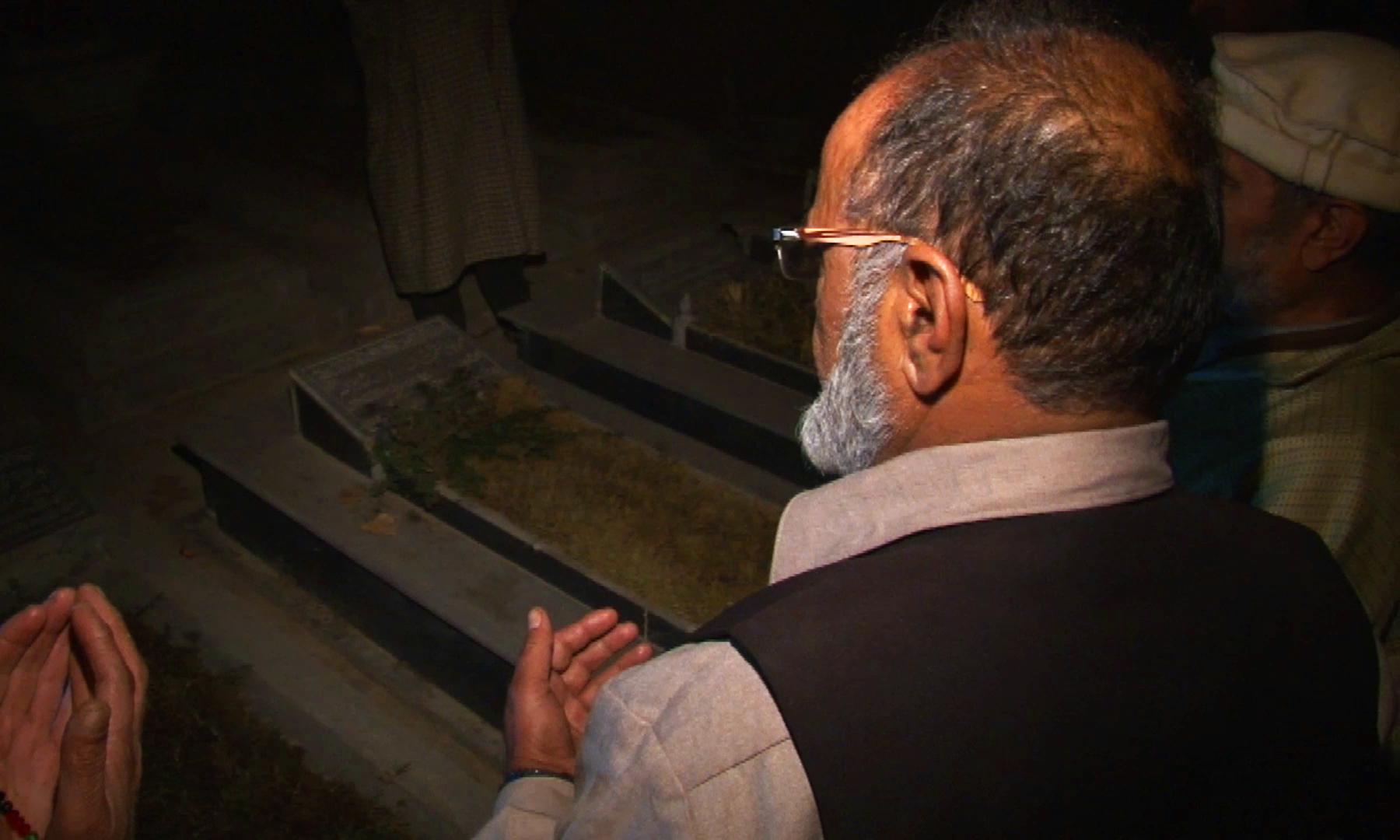 محمد اشرف اپنی والدہ کی قبر پر فاتحہ خوانی کر رہے ہیں — تصویر نوید نسیم