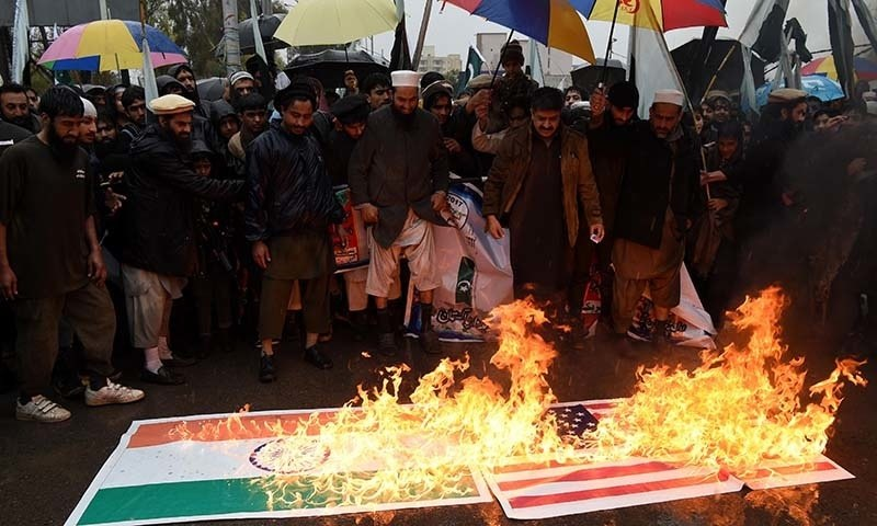 Jamaat-ud-Dawa protesters burn representations of the Indian and American flags as they take part in a protest to mark Kashmir Solidarity Day in Peshawar. ─ AFP