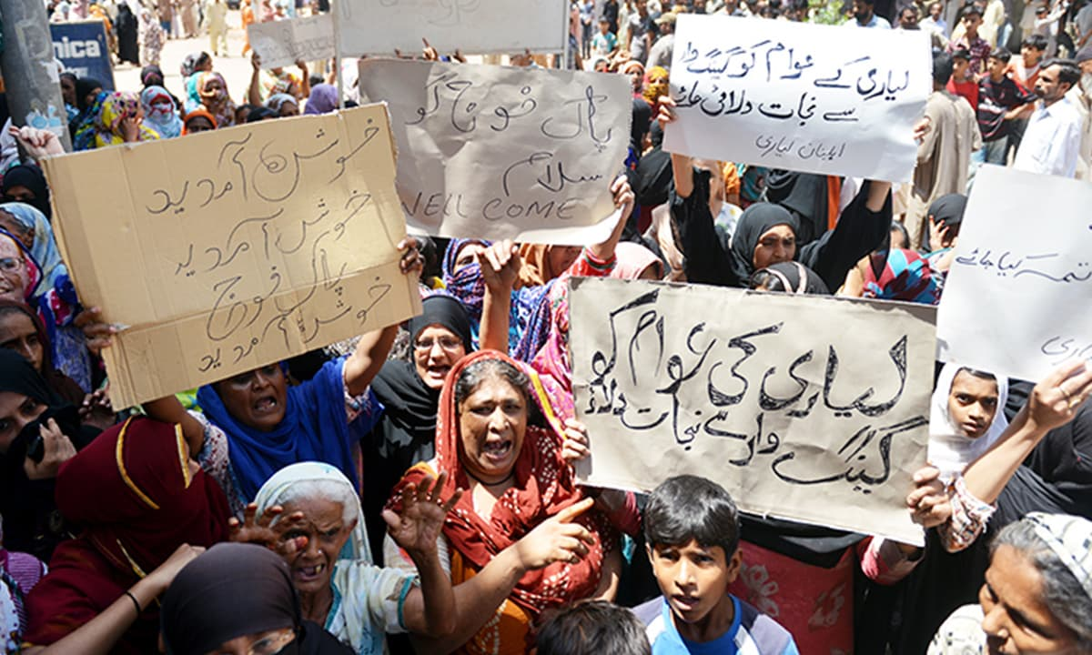 Women holding posters, welcoming the Rangers to Lyari | White Star