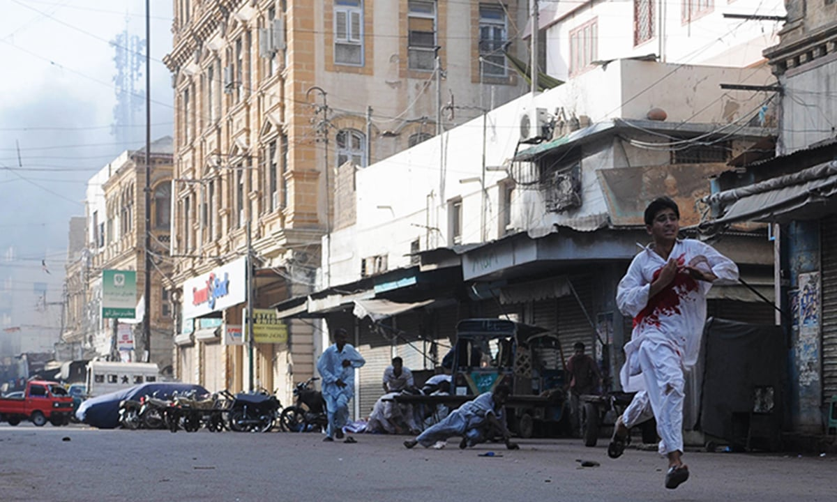 A young man bleeds as he runs for his life, after unknown assilants opened fire at a rally in Lyari in May 2012 | Faysal Mujeeb, White Star