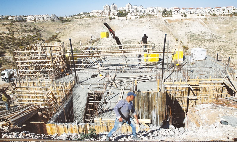 Labourers work at a construction site in the Israeli settlement of Maale Adumim in occupied West Bank on Tuesday.— Reuters