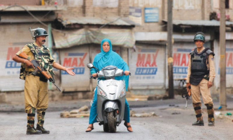 A woman in Kashmir is stopped by Indian paramilitary forces. —AP
