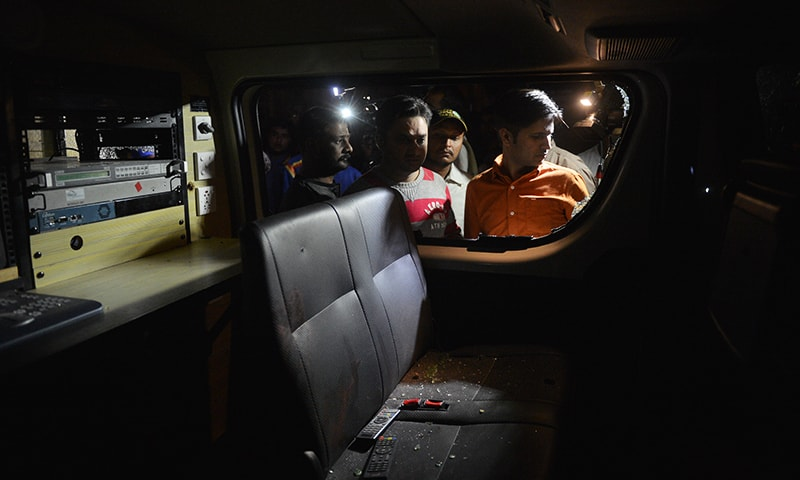 People look into the damaged Samaa TV van after the attack.— AFP