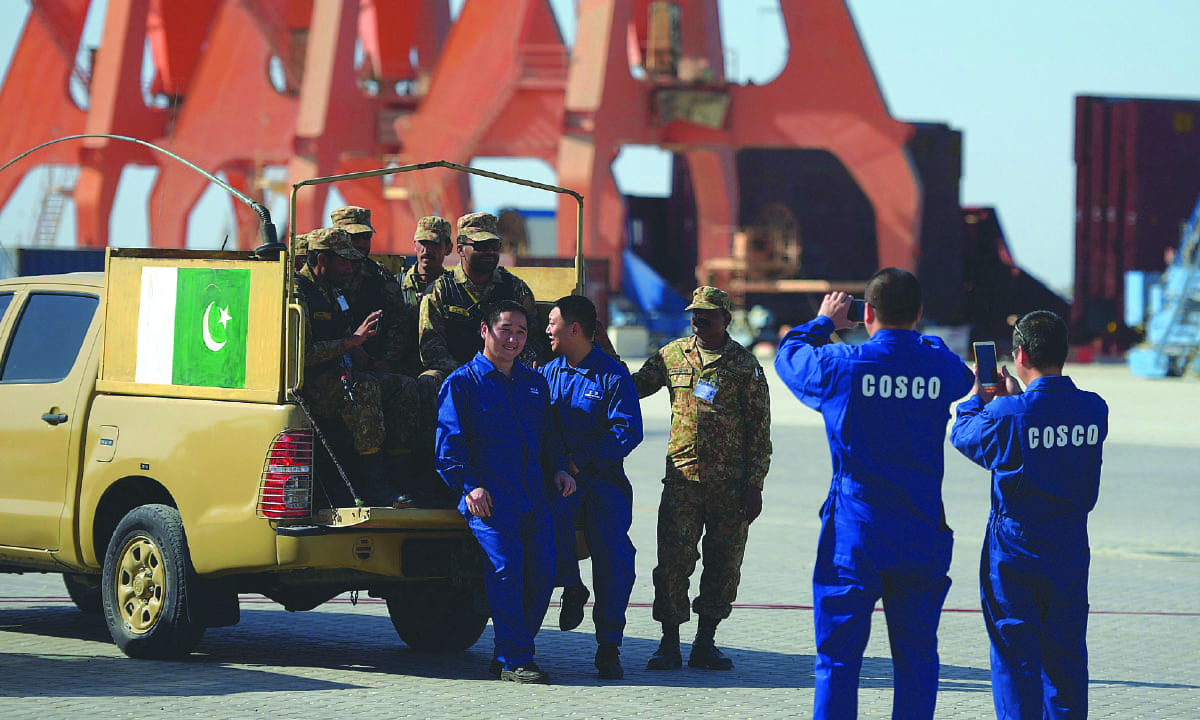 Crew members of a Chinese ship take pictures with Pakistani security officials in Gwadar | AFP