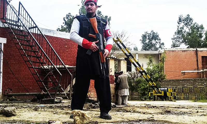 A security officer stands alert at the site of a bombing in Ghalanai area of Mohmand.—AP.