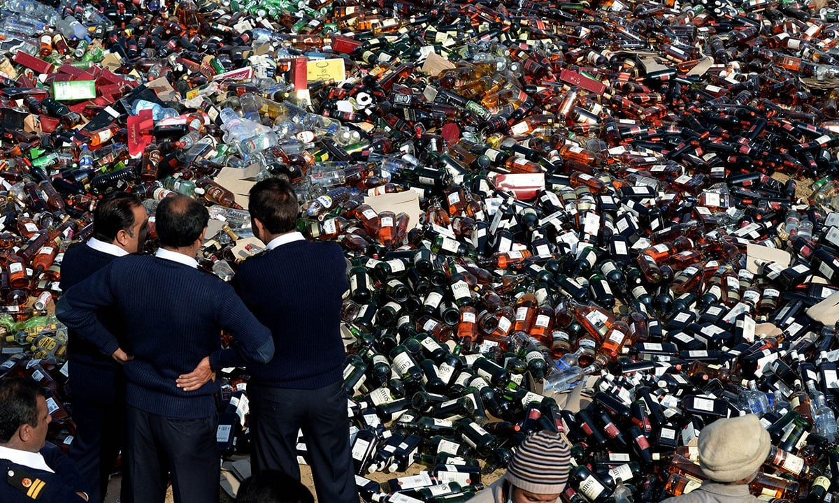 Pakistani customs officials watch over bottles of liquor before destroying them in Lahore | AFP