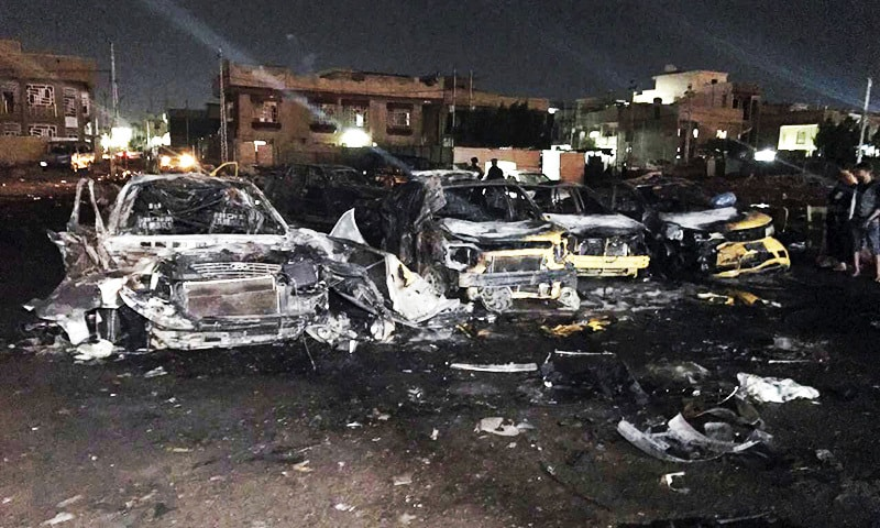 Civilians gather at the site of a car bomb in a used car dealer's parking lot in Baghdad.—AP