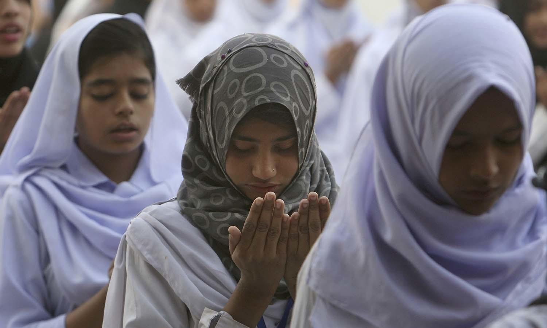 سیہون میں خودکش دھماکے میں ہلاک ہونے والے افراد کے لیے اسکولوں کے طلبہ نے دعائیں کیں — فوٹو/ اے پی