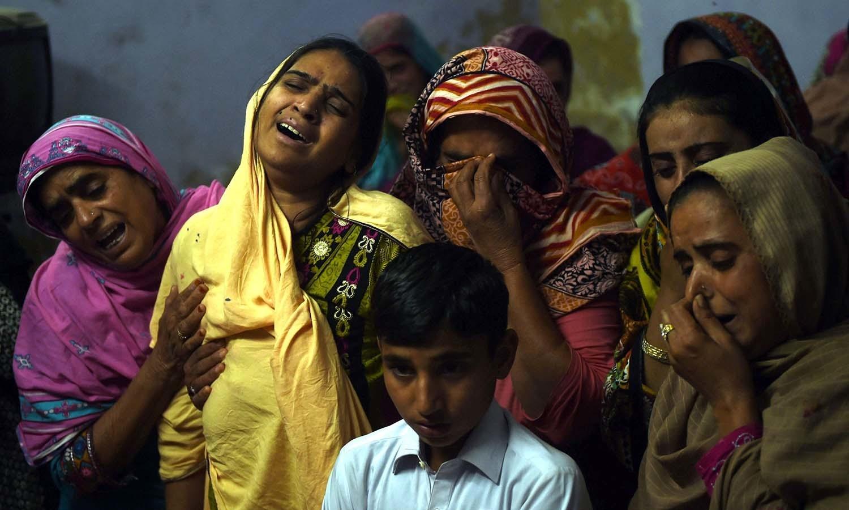 مزار پر ہونے والے دھماکے میں ہلاک ہونے والے 13 سالہ ذیشان کی ماں کو دیگر افراد دلاسا دیتے رہے — فوٹو/ اے ایف پی