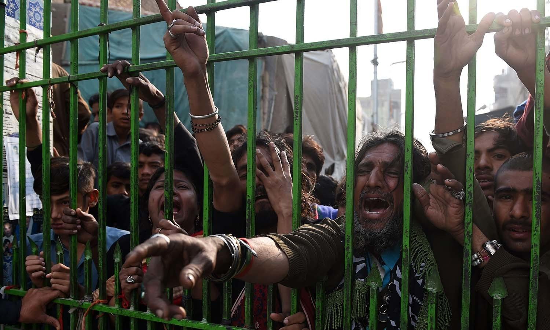 دھماکے کے بعد زائرین کی بڑی تعداد درگاہ کے سیل دروازوں اور رکاوٹوں کو توڑ کر اندر داخل ہوئی — فوٹو/ اے ایف پی