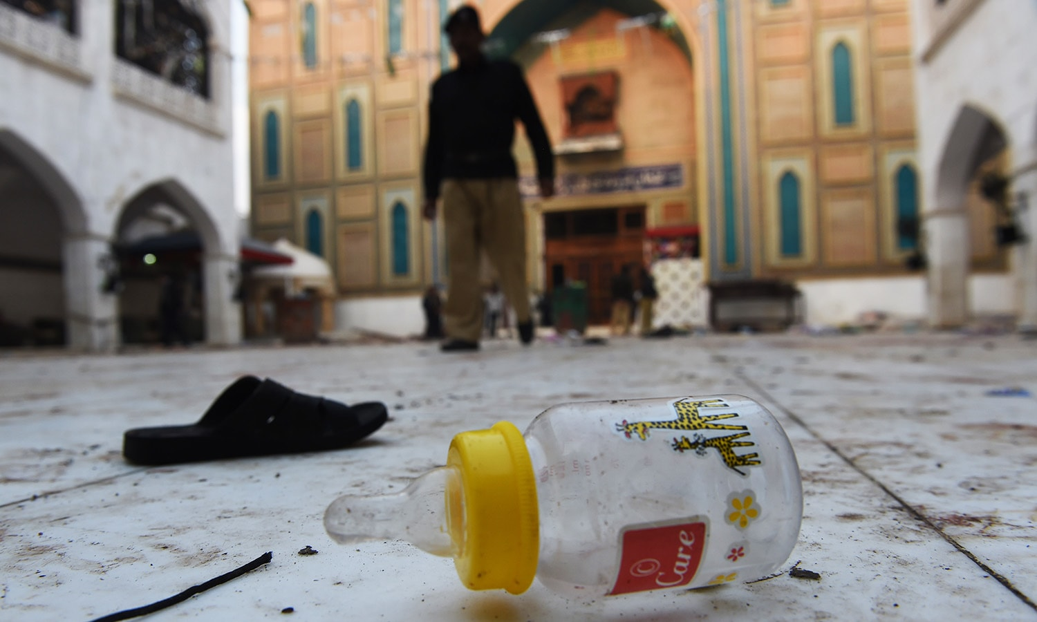 Slippers and a baby feeder of blast victims lie on the ground at the 13th century Muslim Sufi shrine of Lal Shahbaz Qalandar. — AFP