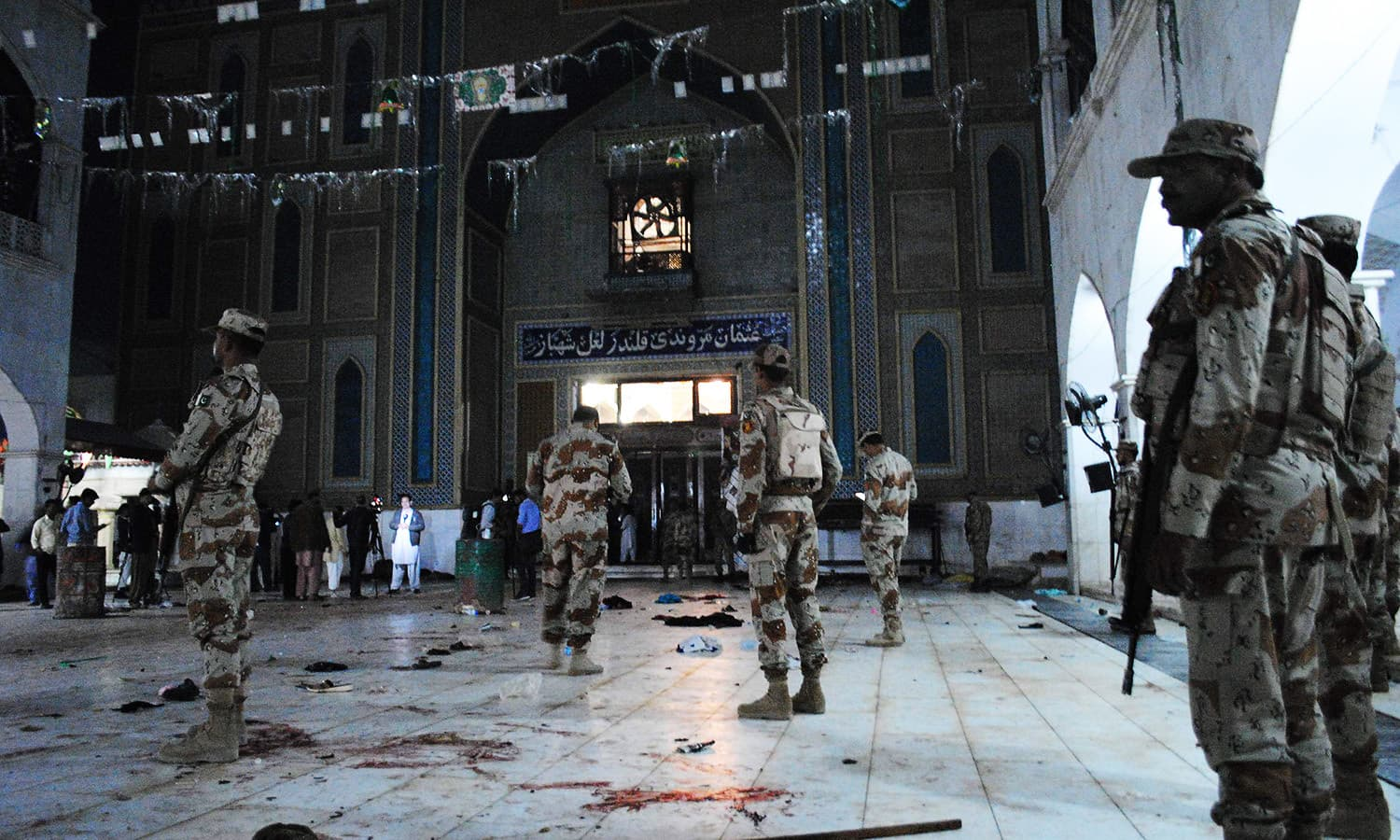 Pakistani para-military soldiers stand alert at the shrine of 13th century Muslim Sufi Saint Lal Shahbaz Qalandar, after a bomb blew up in the town of Sehwan.─AFP