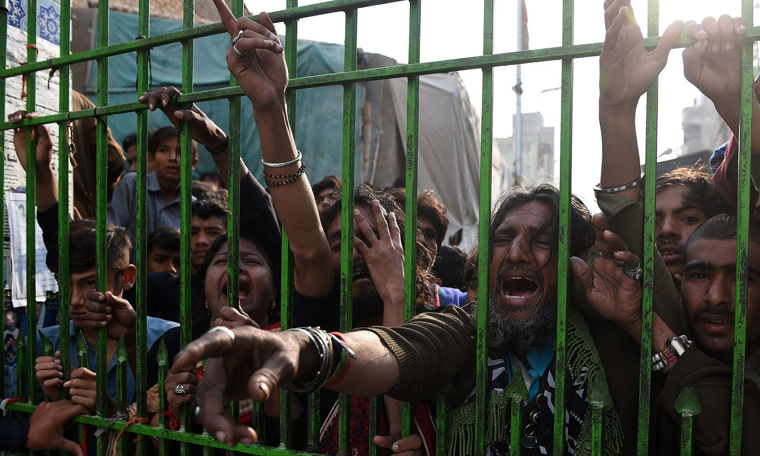 Pakistani devotees react as they gather outside the closed gate of the shrine of 13th century Muslim Sufi saint Lal Shahbaz Qalandar a day after a bomb blast. ─AFP