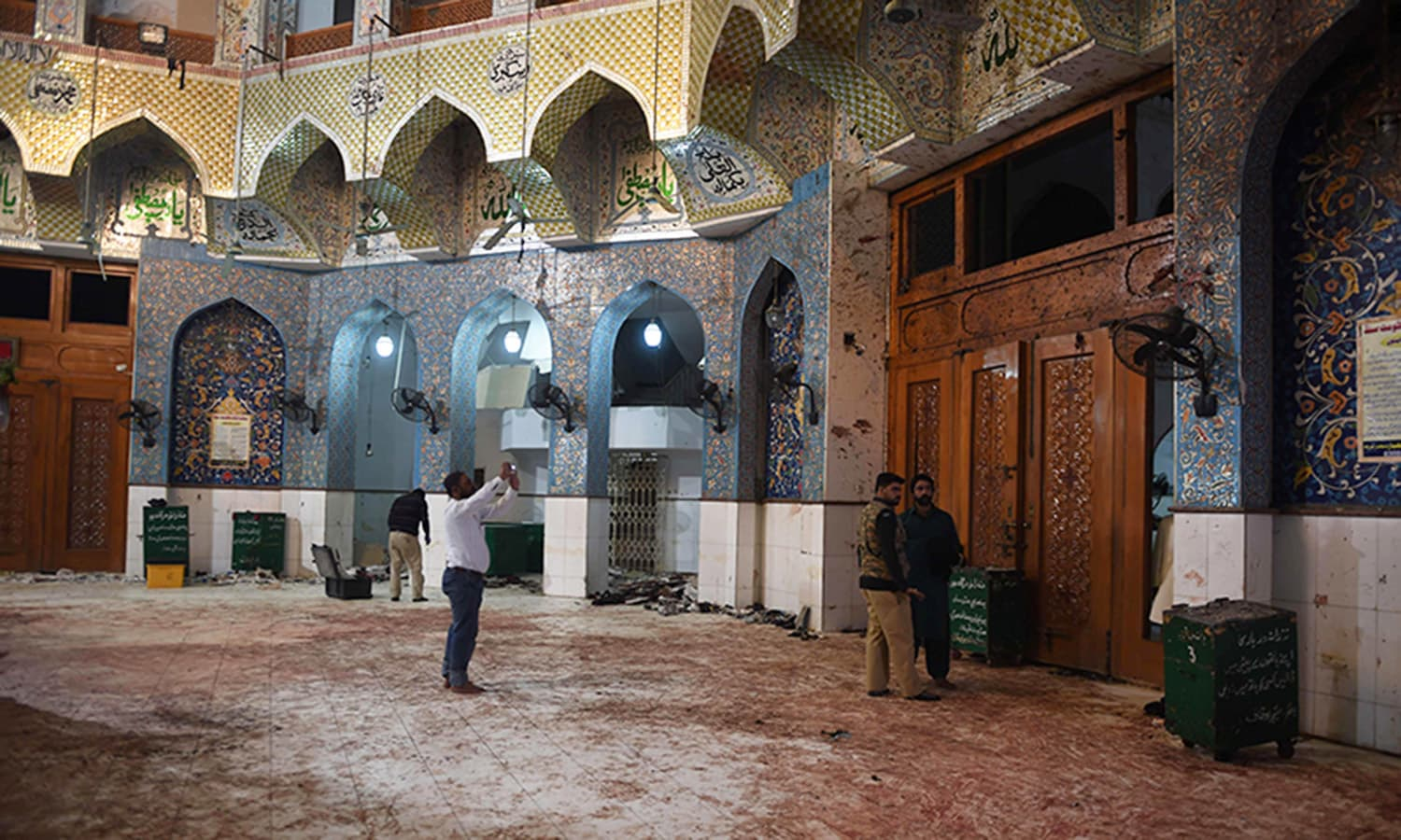 Pakistani security officials inspect the blood-stained floor a day after a bomb attack hit the Lal Shahbaz Qalandar shrine in Sehwan. ─AFP