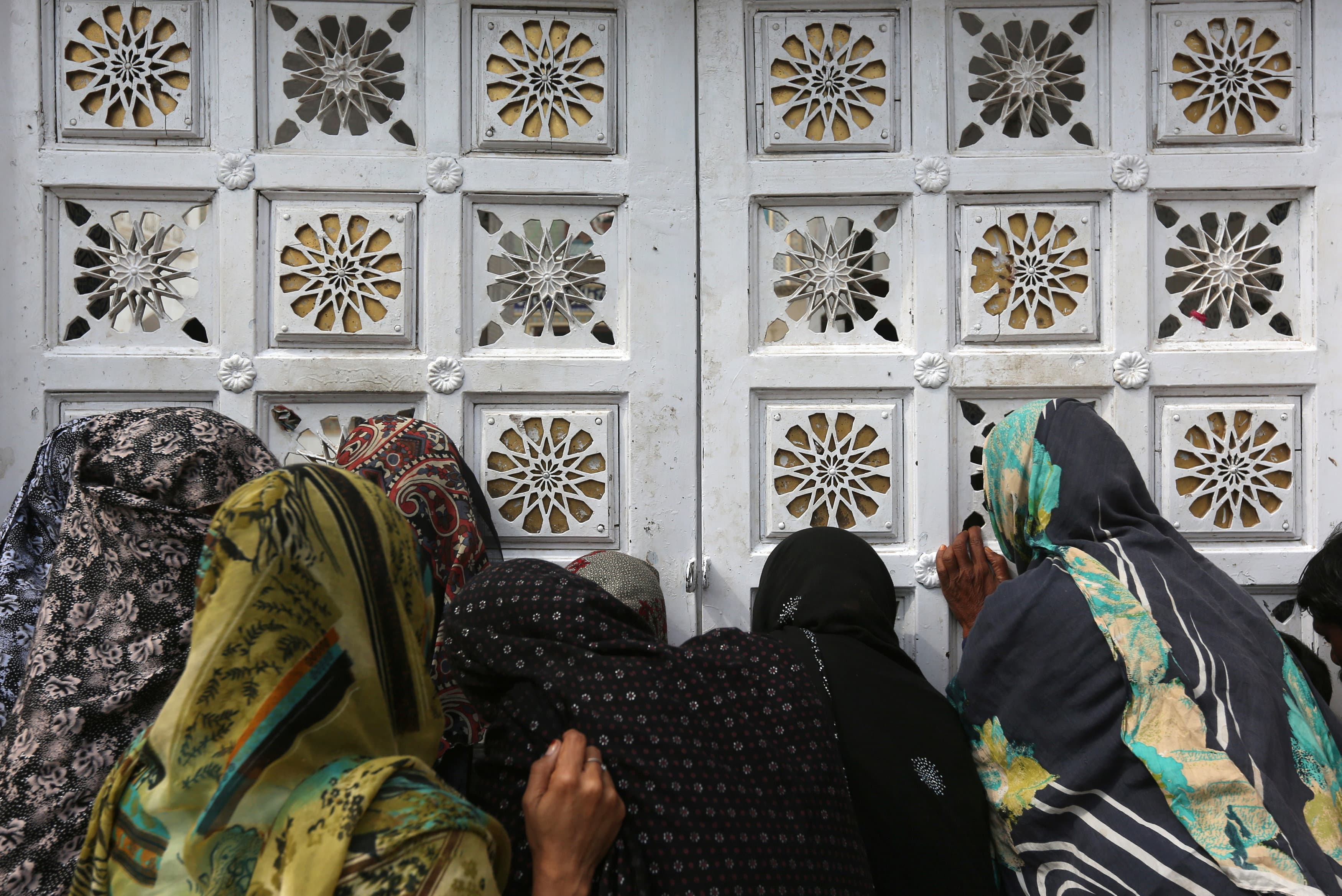 Women devotees gather outside a closed entrance of a hall to get in to search for their belongings at the shrine post the blast.─Reuters