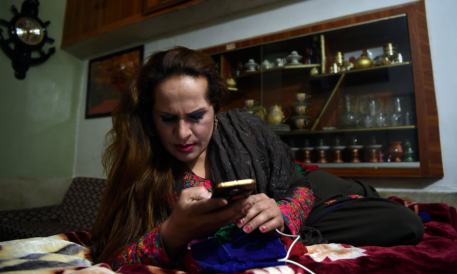 Farzana, a member of the Pakistani transgender community, checks her mobile telephone at her home in Peshawar.─AFP