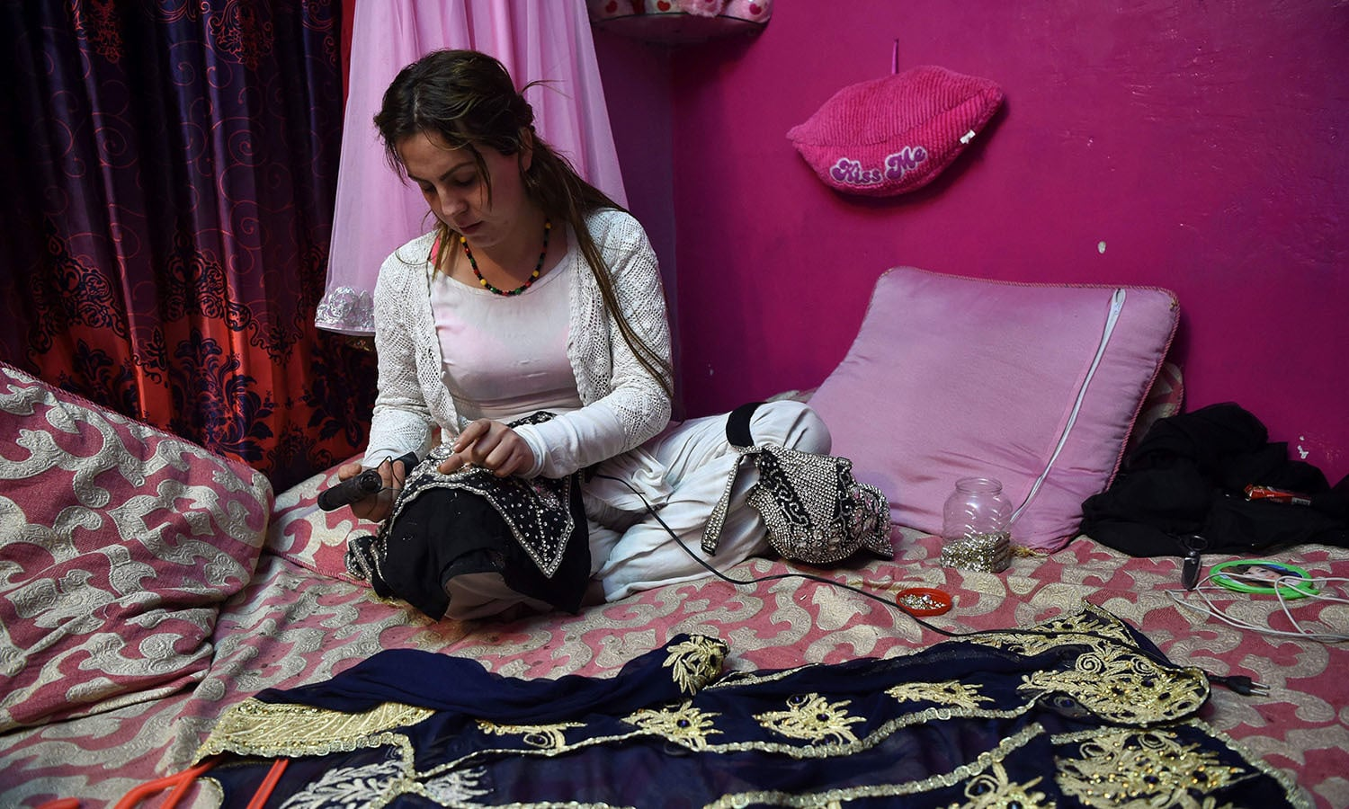 Paro, a member of the Pakistani transgender community, designing embroidery on dresses for their community members at her residence in Peshawar.─AFP