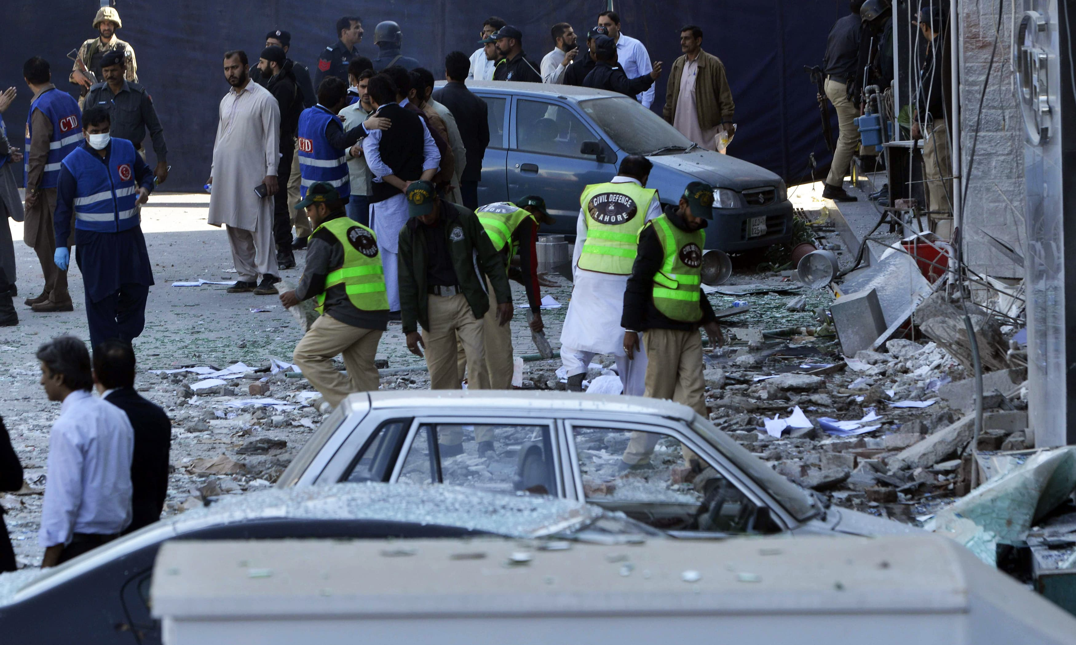 Officials examine the site after the bomb attack in Lahore. —AFP