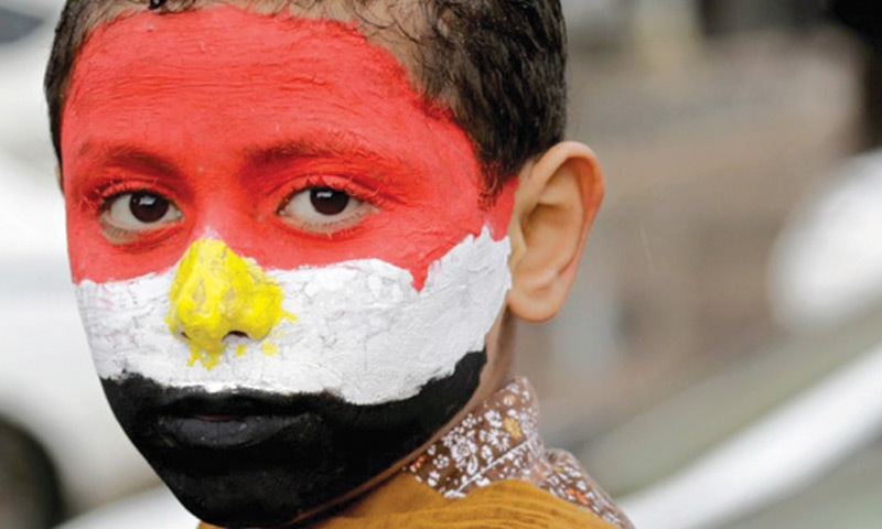 An Egyptian boy wears the colours of the national flag on the anniversary of the 2011 uprising in Tahrir Square, Cairo. — AP