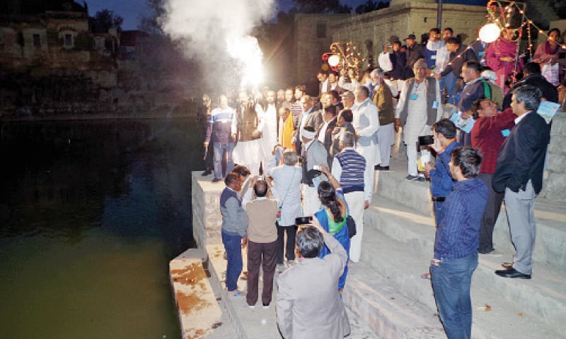 Indian pilgrims and their Pakistani hosts light fireworks in jubilation at Katas Raj to celebrate Shivaratri .— Dawn
