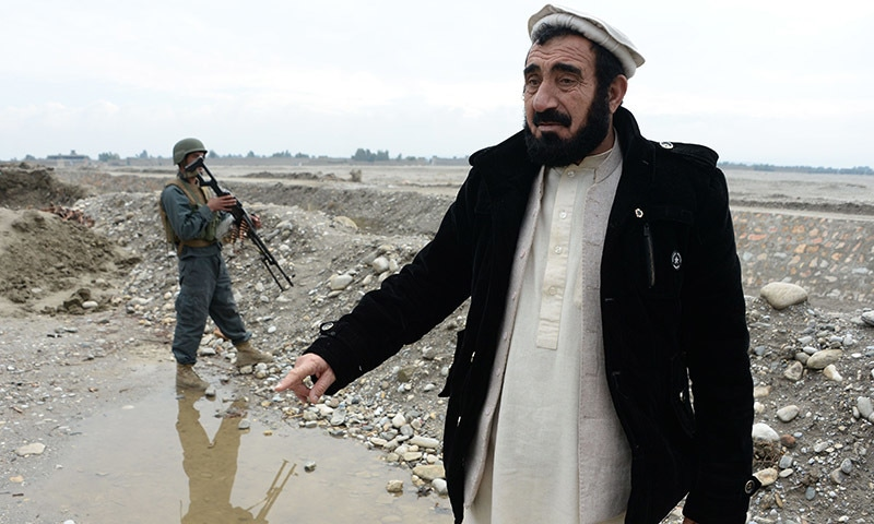 Haji Ghalib walks with an escort as he inspects security outposts in Bati Kot. ─AFP