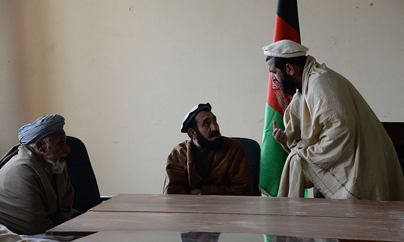 Haji Ghalib speaks with tribal elders in his office in Bati Kot.─AFP