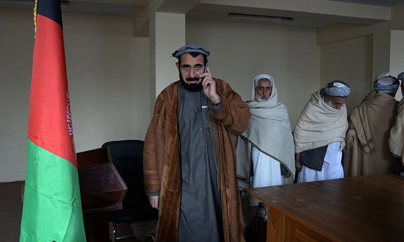 Haji Ghalib (C) who was imprisoned for five years at Guantanamo Bay, speaks on his telephone as he prepares to meet tribal elders in his office in Bati Kot.─AFP