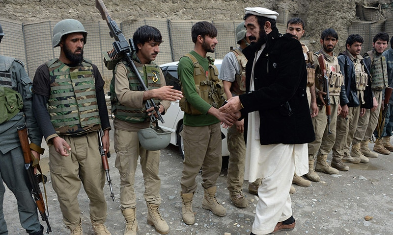 Haji Ghalib speaks with soldiers as he inspects security outposts in Bati Kot.─AFP