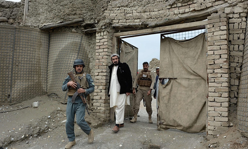 Haji Ghalib (C) walks with officials as he inspects security outposts in Bati Kot.- AFP