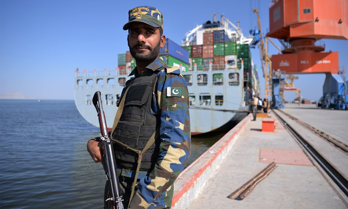 A Pakistani Naval personnel stands guard beside a ship carrying containers | AFP