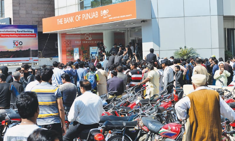LAHORE: Cricket fans wait in long queues outside a Bank of Punjab branch to buy PSL final tickets on Thursday.— M Arif/White Star