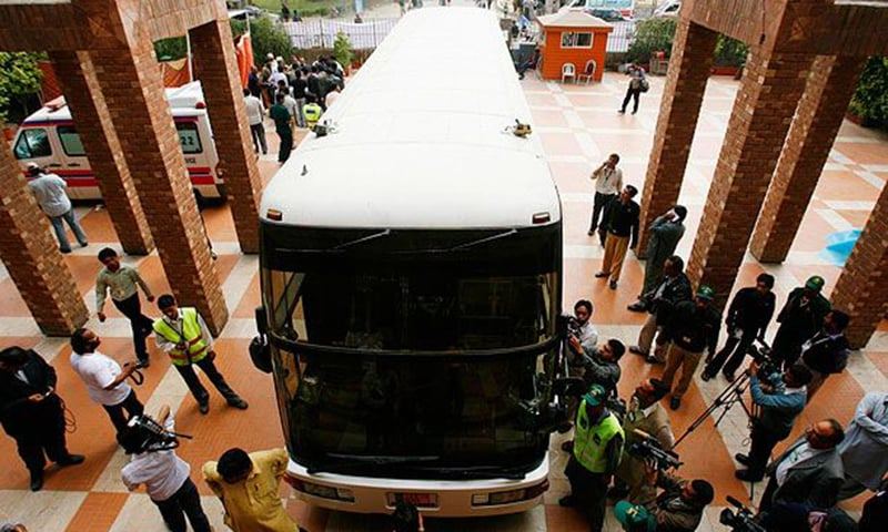 Members of the media gather around a bus, which was carrying the Sri Lankan cricket team, parked outside the Qadhafi stadium in Lahore.— Reuters