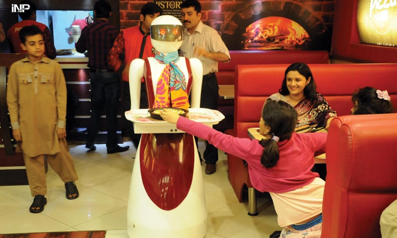 MULTAN: A robot waiter serves a pizza to customers at Pizza.com restaurant.—INP